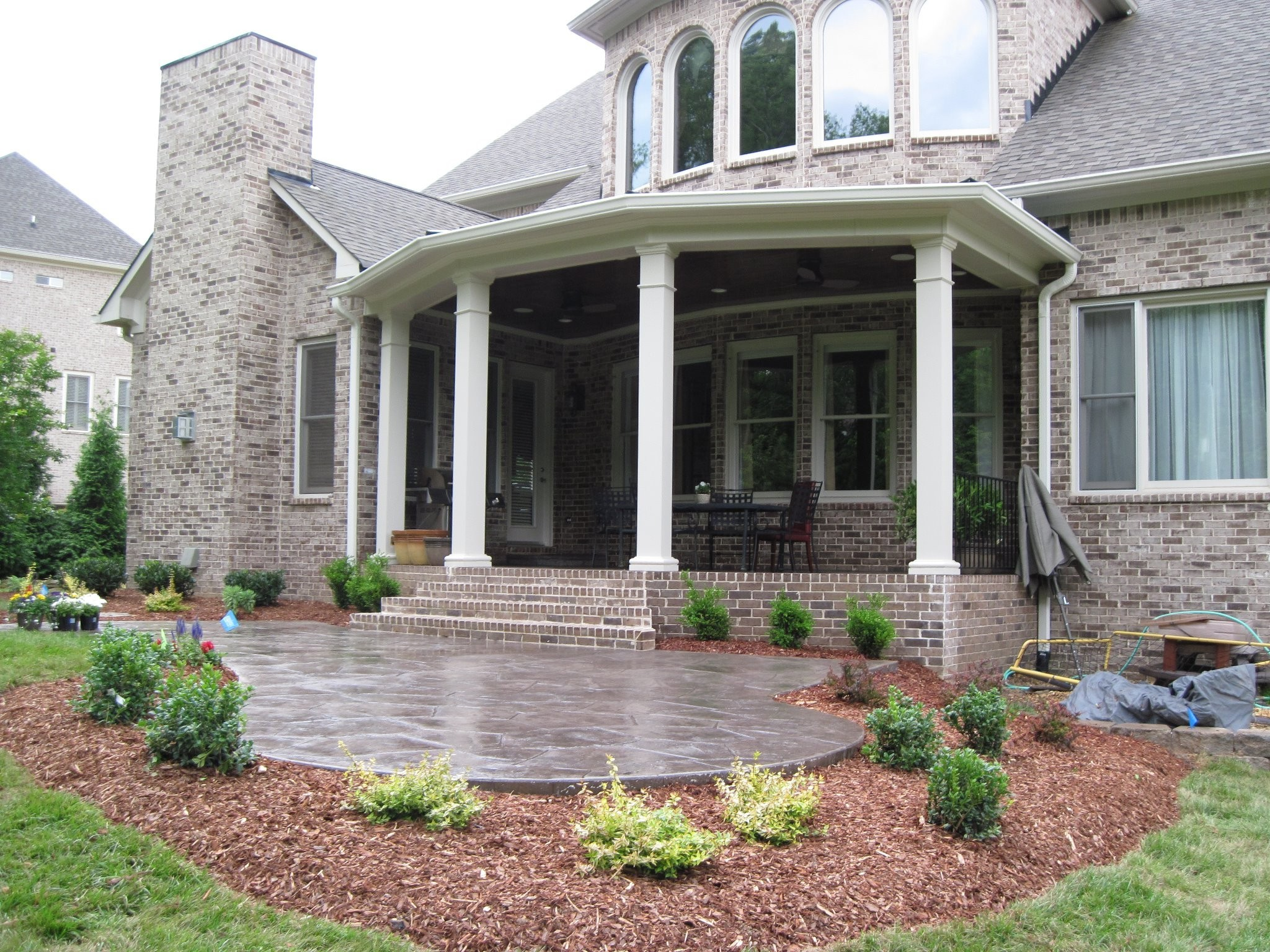 Raised Patio With Covered Porch And Stamped Concrete